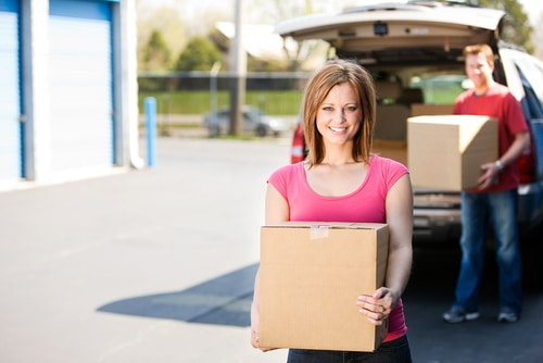 Woman holding box with man holding a box in background