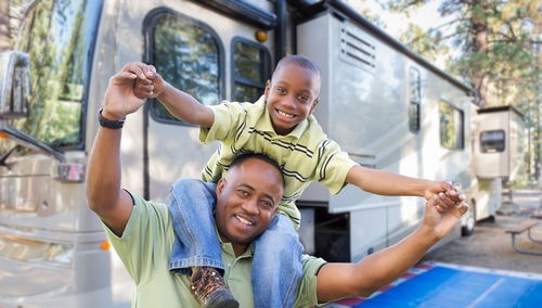 African American Man with Son in front of an RV